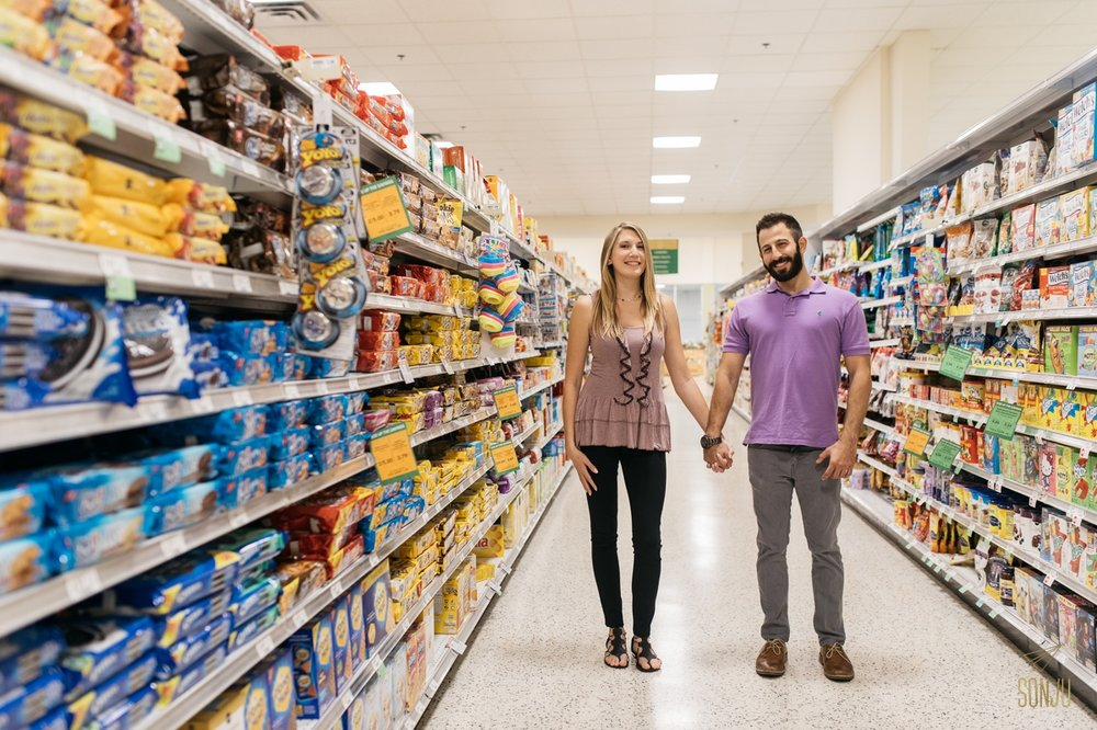 Newly engaged couple hold hands in cookie aisle in Publix