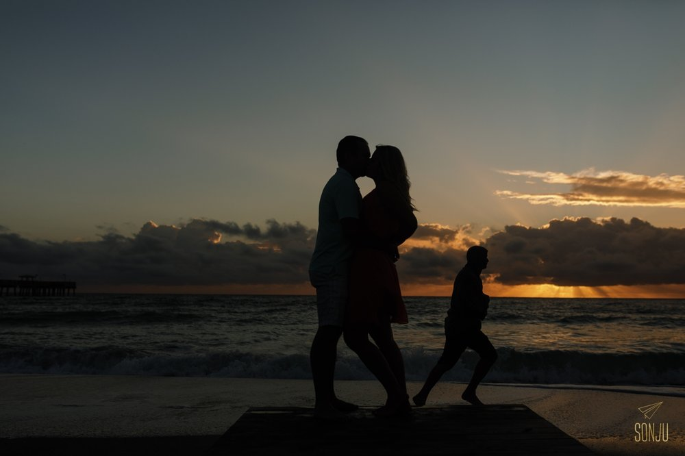Jogger photobombs couple posing for silhouette on Fort Lauderdale beach at sunrise