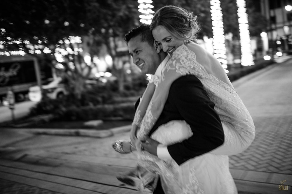 Groom gives bride piggyback at the end of their wedding night in Fort Lauderdale Florida