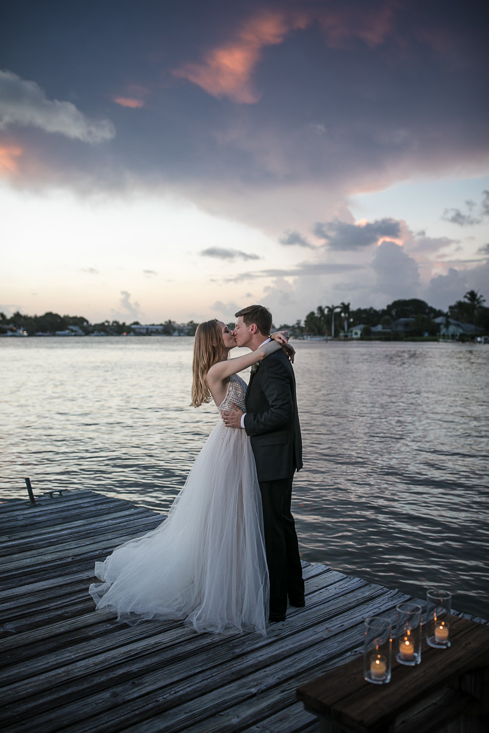 Bride and groom embrace on a dock outside their backyard wedding in Jupiter Florida