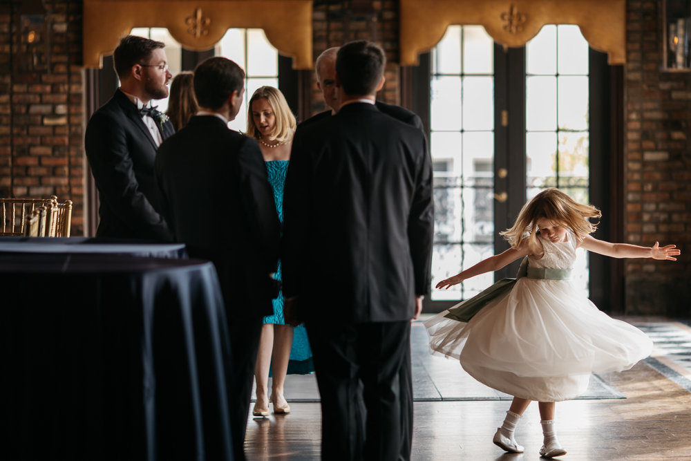 Flower girl spins around and dances while adults ignore her before a wedding at the Cruz Building in Miami Florida
