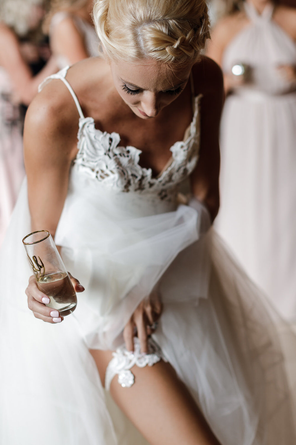 Bride adjusts her garter while holding a glass of champagne before her wedding ceremony at the Addison in Boca Raton, Florida.