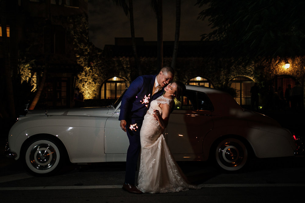 Bride and groom pose with sparklers and vintage car outside the Coral Gables Country Club at the end of their wedding reception