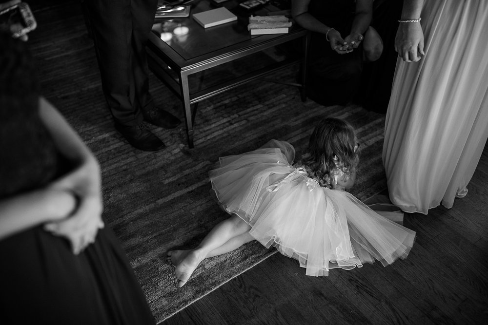 Dis-interested flower girl lays on the floor before the wedding ceremony at the Addison in Boca Raton Florida