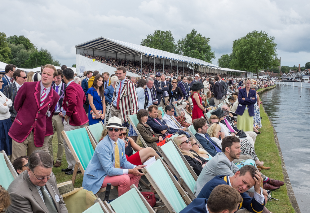 Spectators in the Steward's Enclosure line the banks at Henley Royal Regatta. A strict dress code applies: Jacket and tie for men, skirts or dresses below the knee for women.