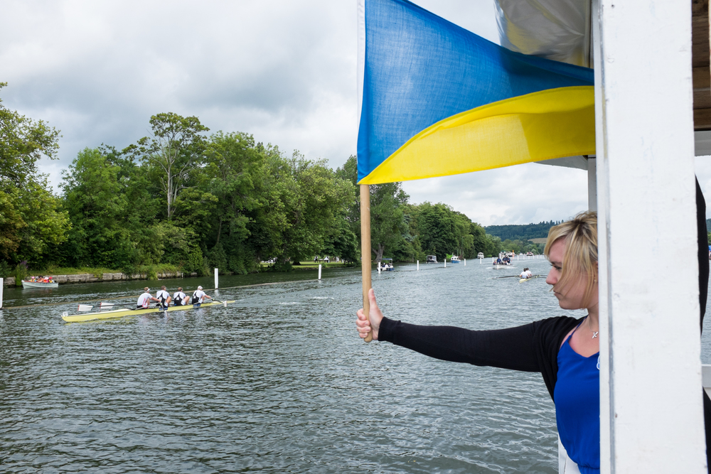 A signaller at Henley Royal Regatta drops a timing flag during a race as the leading crew passes the 1-mile point. A timekeeper on the umpire's launch following will make a note of the split time, and announce it to the crowds in the grandstands.