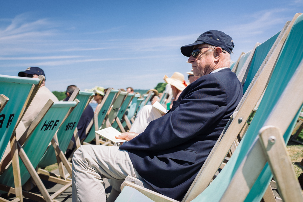 A spectator relaxes in the heat of the midday sunshine in the Steward's Enclosure at Henley Royal Regatta. Men are not allowed to take off their jackets, despite the temperature, unless a special announcement is made by officials.