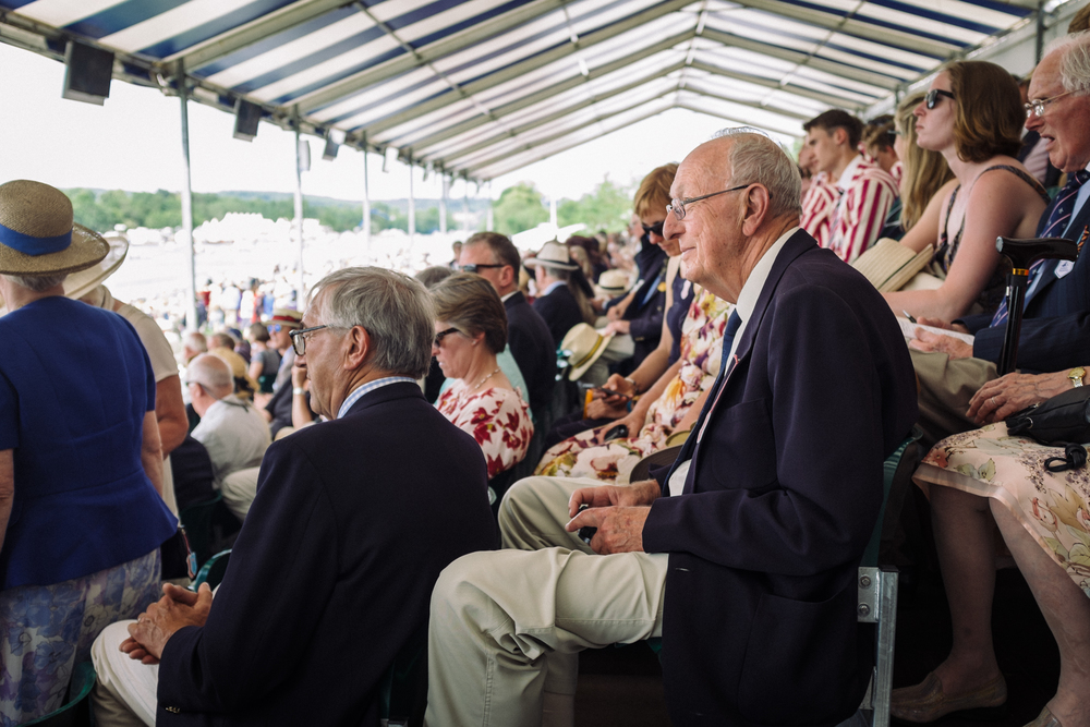 A spectator at Henley Royal Regatta enjoys the view from the grandstands.