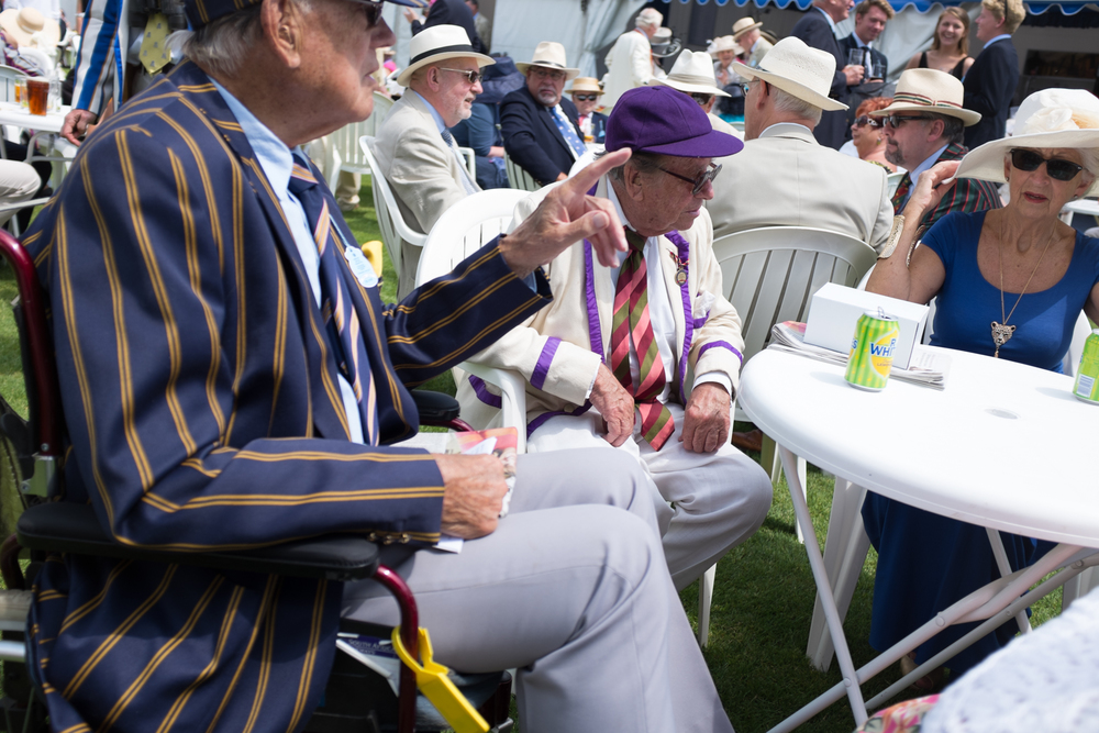 Catching up over drinks at the Bridge Bar at Henley Royal Regatta. Lots of spectators have been coming to the regatta for a great many years, and still wear their club colours with pride.