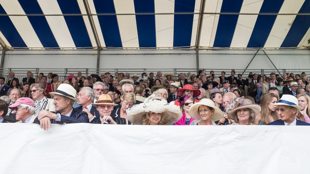 Spectators in the Steward's Enclosure grandstand at Henley Royal Regatta.
