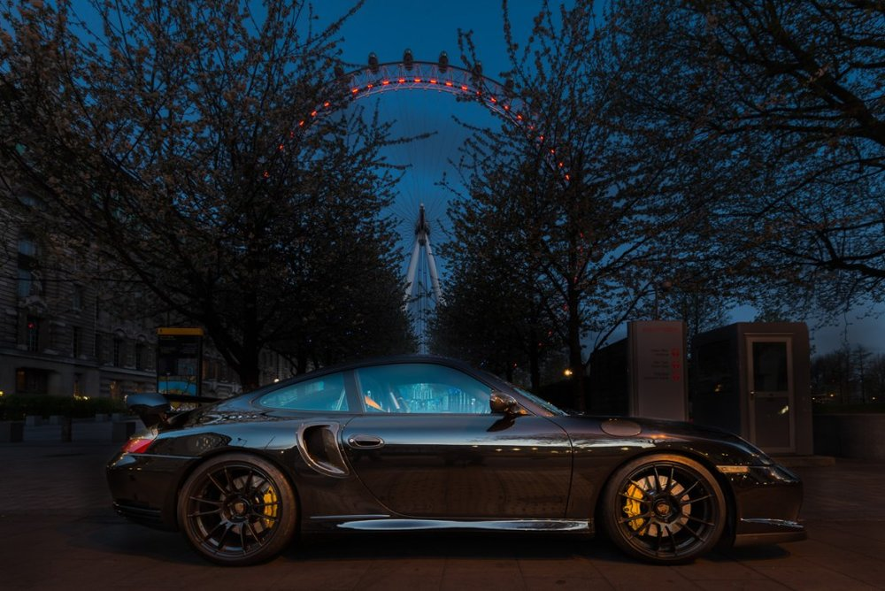Porsche 996 parked at night with the London Eye in the background.