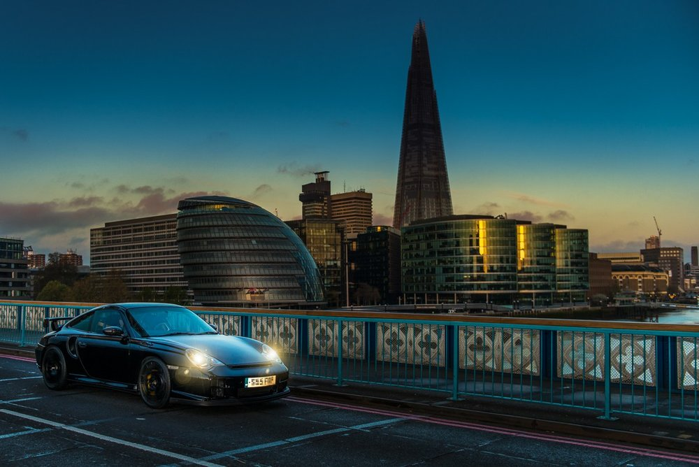 Porsche 996 driving over London Tower Bridge with the Shard lit up with the sunrise