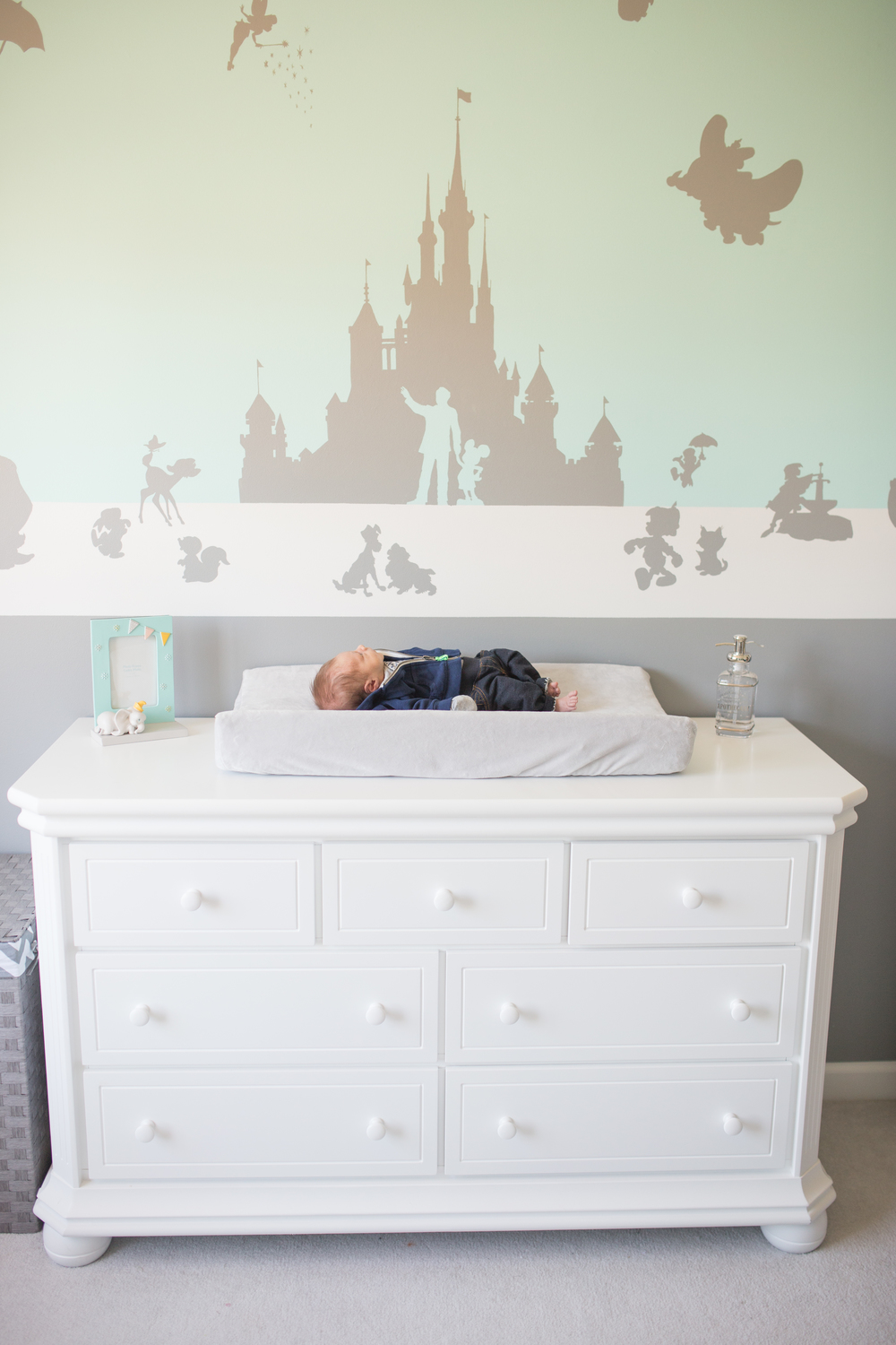Newborn on changing table in Disney Nursery in Massachusetts
