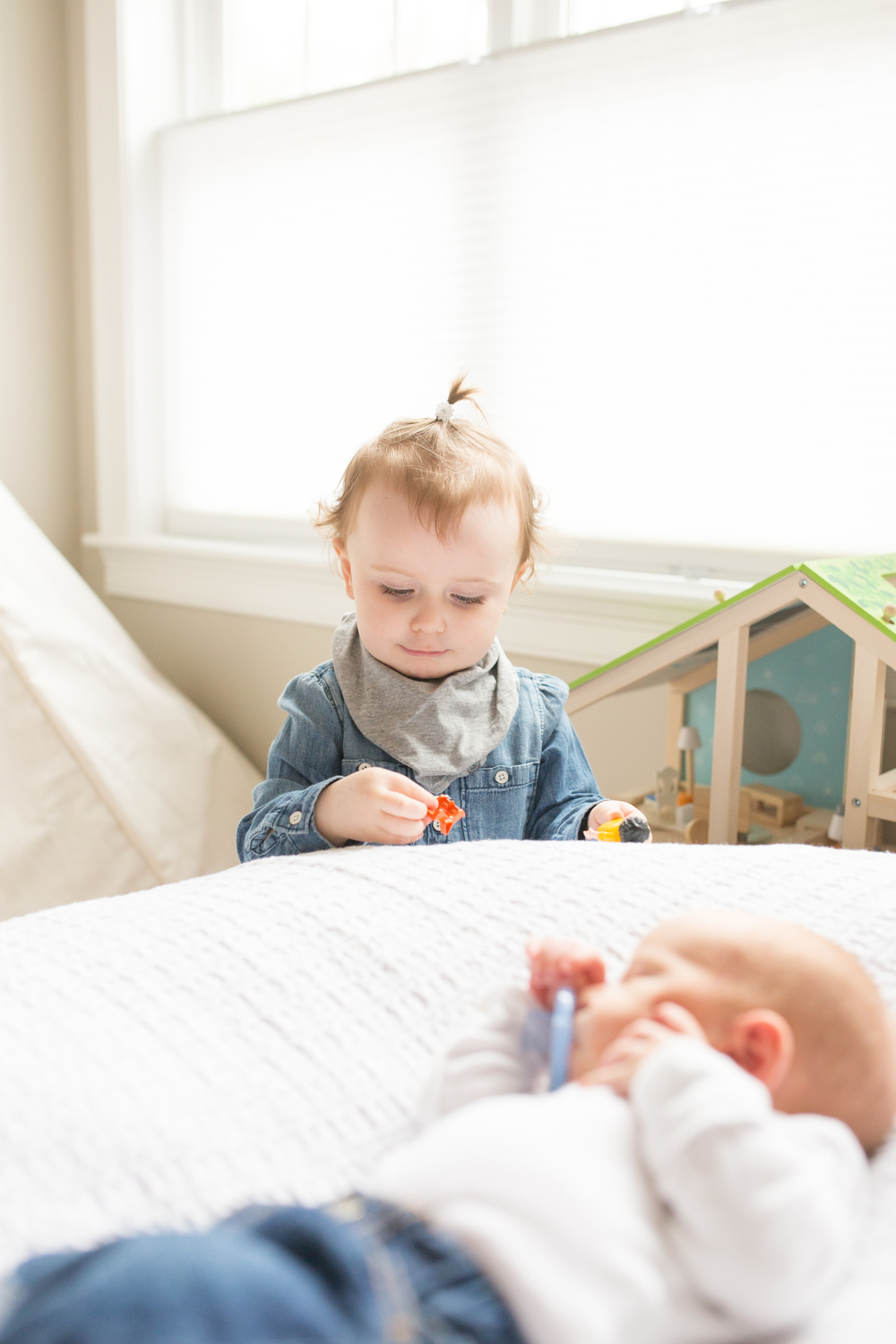 Toddler playing with newborn in-home relaxed session in Boston Massachusetts