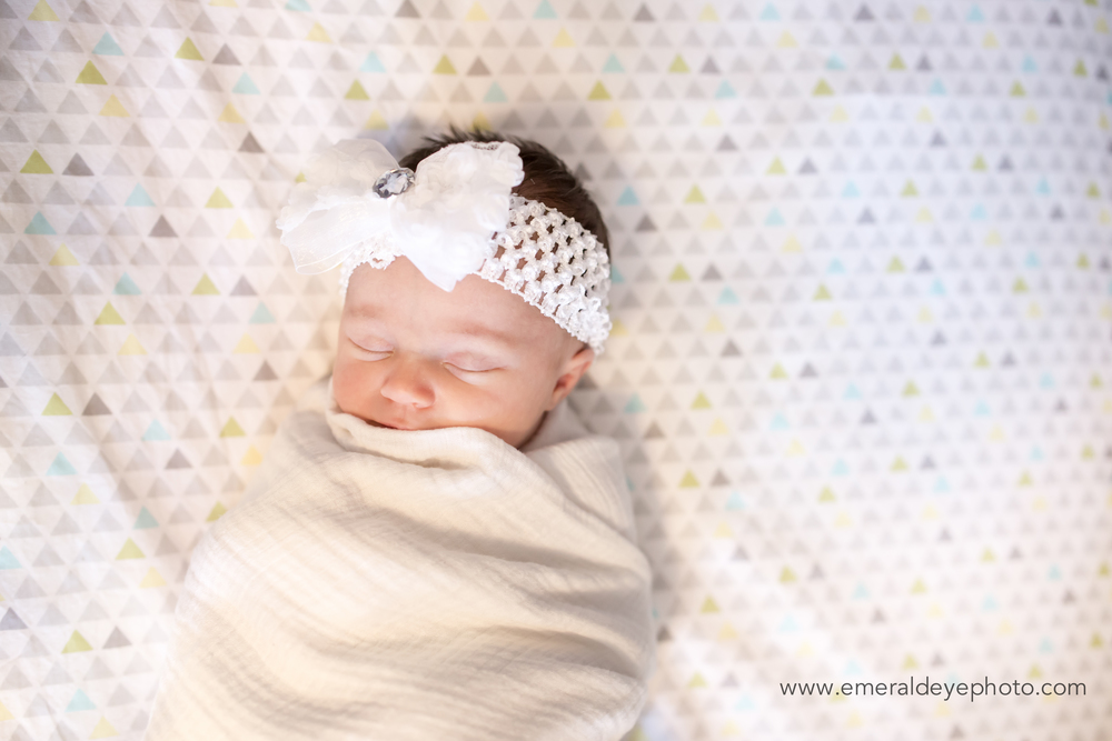 New baby girl sleeping in crib with bow in Boston Massachusetts