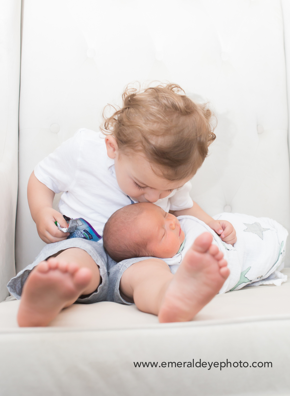 Toddler kisses baby brother during LIfestyle session in Massachusetts