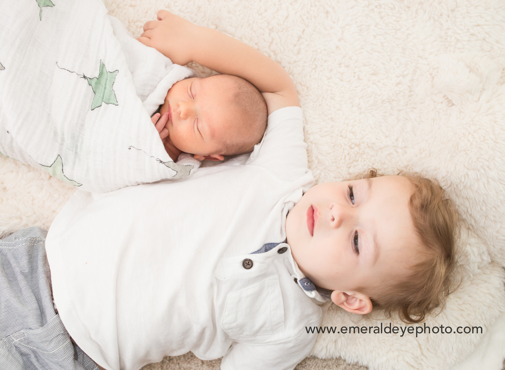 Toddler lays with his baby brother during Lifestyle session in Boston Massachusetts