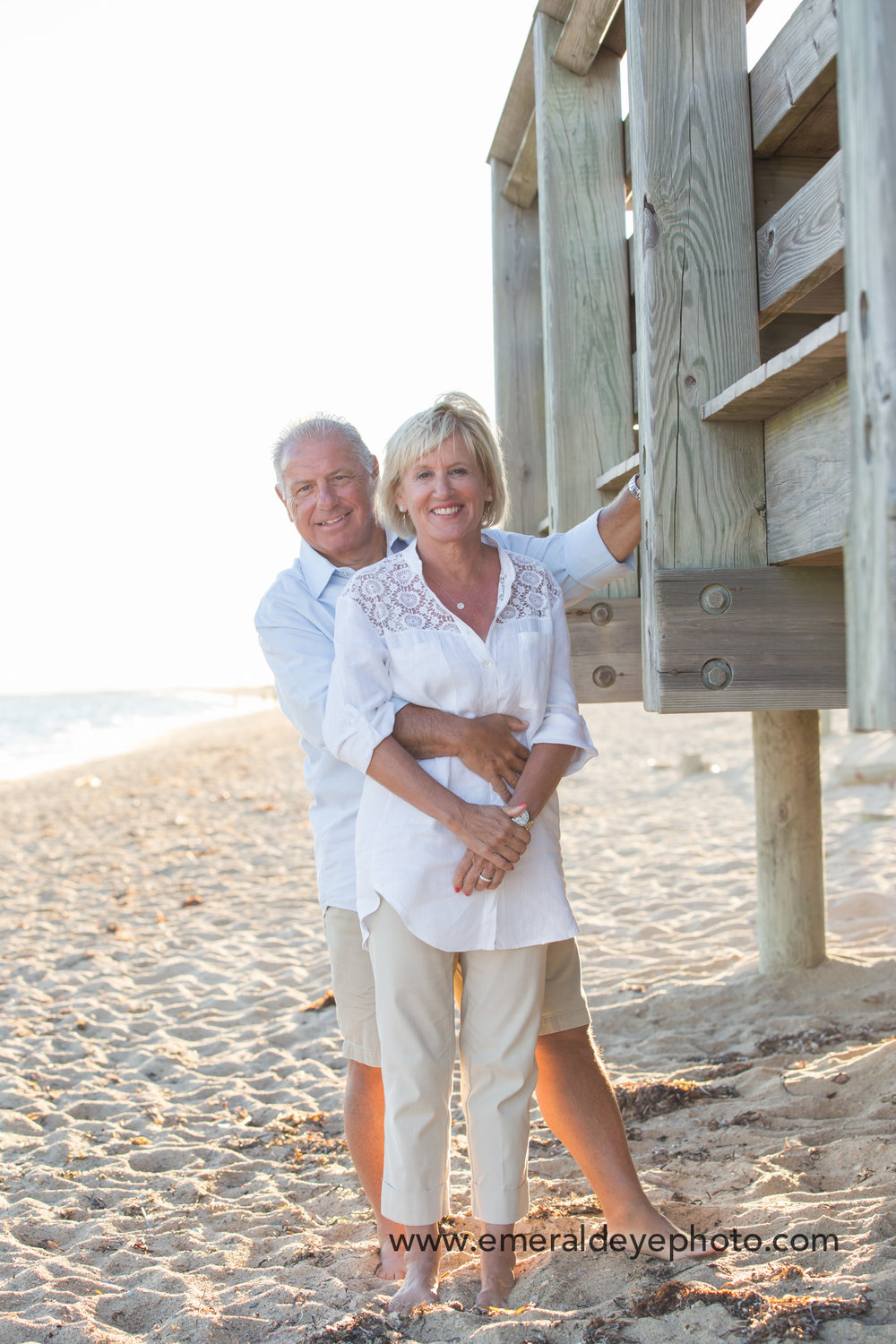 Grandparents stand on South Cape Beach at sunset in Mashpee Massachusetts