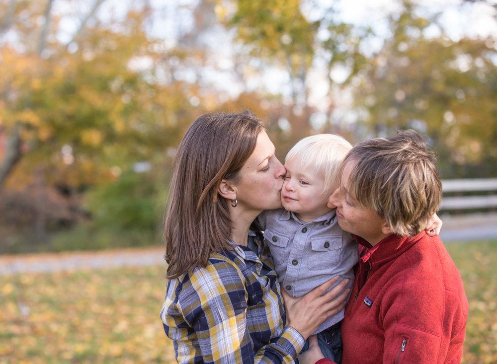 Moms kissing toddler during family photos in Bridgewater Massachusetts