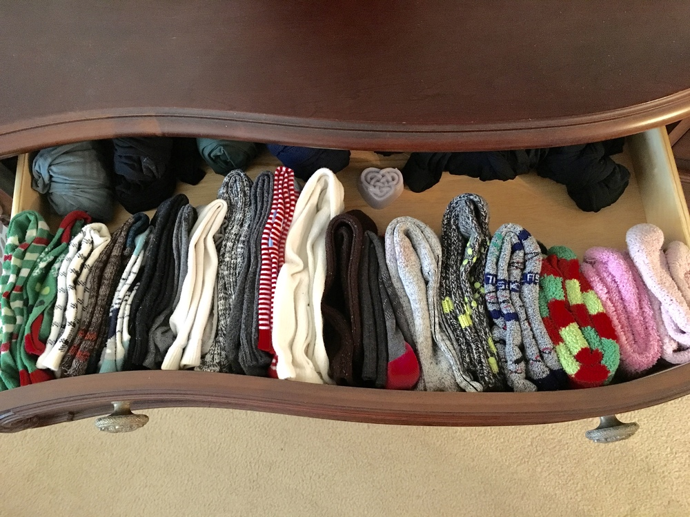 If you have shallow drawers this is a great way to make use of the vertical space, but still be able to see what you have and save your horizontal space. Simply pair your socks and fold in half. Then stand them on their sides so you can see each pair! Works great for boot socks and those fuzzy, cozy socks you wear on winter nights. You can use the space at the back of the drawer for all those tights that only get worn a few times a year.  I still roll my ankle socks to keep the pairs together and make them a little faster to grab. Whether you roll or fold socks, I highly recommend matching them up (or mismatching them up if that's your thing) as soon as they come out of the laundry so that when you're hurrying to get ready in the morning you don't have to waste time trying to find mates!