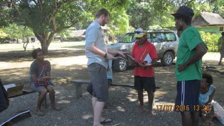 Dylan Gaffney presenting booklets to Kubei Balifun (community leader) at Bilbil village, Madang, PNG.  Photo: Dylan Gaffney, 2016.