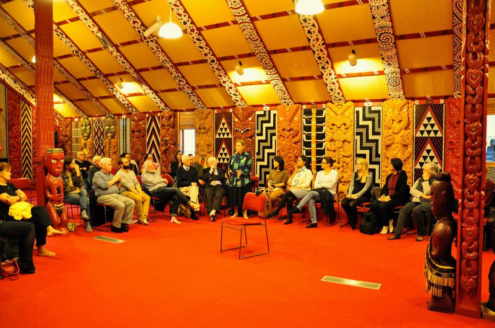 Dame Dr. Joan Metge (standing) during the marae kōrero at Te Tumu Herenga Waka. Bernie Kernott is seated to the left, and Te Range Hīroa is to the far left.