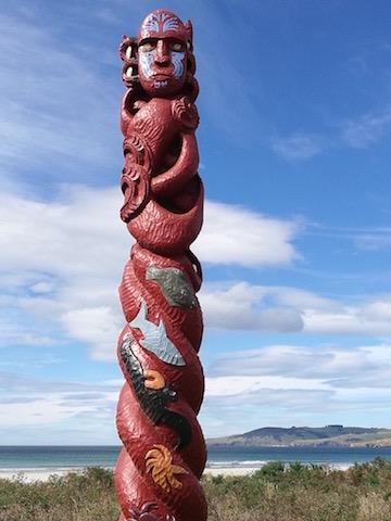 Takaroa/Tangaroa. Carved pou at Warrington Beach, Dunedin.Carved by members of Te Whare Wananga o Te Whānau Arohanui, Watiati, Dunedin, the spirals represent the past, present, and future generations of kaitiaki for the resources around the East Otago coastline—the domain of Takaroa. It stands at the interface between sea and land.  Photo: Lyn Carter.