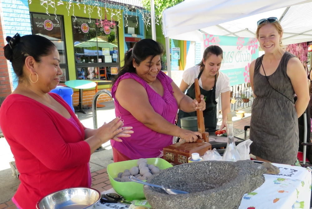 Marcella helps with a cooking activity at The Forest Grove Farmers MArket Last Year.