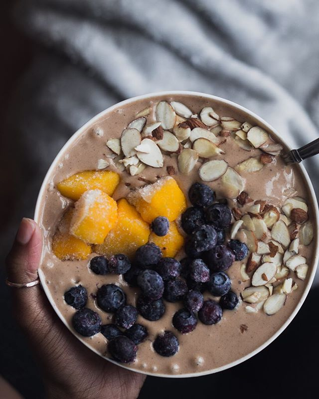 Monday Mood // chocolate for breakfast...girl needed a loaded protein bowl to fuel these achy 🍑 muscles (excuses 🤫). Today's goal is to park myself next to inanimate object & hope no one asks me to move. You go kick Monday's butt!  #inmybowl // 2 frozen bananas • 1 scope of @purelyinspirednutrition organic decadent chocolate protein • 1 cup of @almondbreeze almond milk • 1 tbsp @wildoatsmarketplace flaxseed for added fiber and protein • 2 tbsp peanut butter • 1 tsp honey •drop of vanilla extract  Topped with almonds, mango, and blueberries...don't forget the blueberries