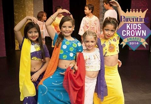 grupo de niñas coloridamente vestidas sonrien y posan en forma de ballet mirando hacia la camara.