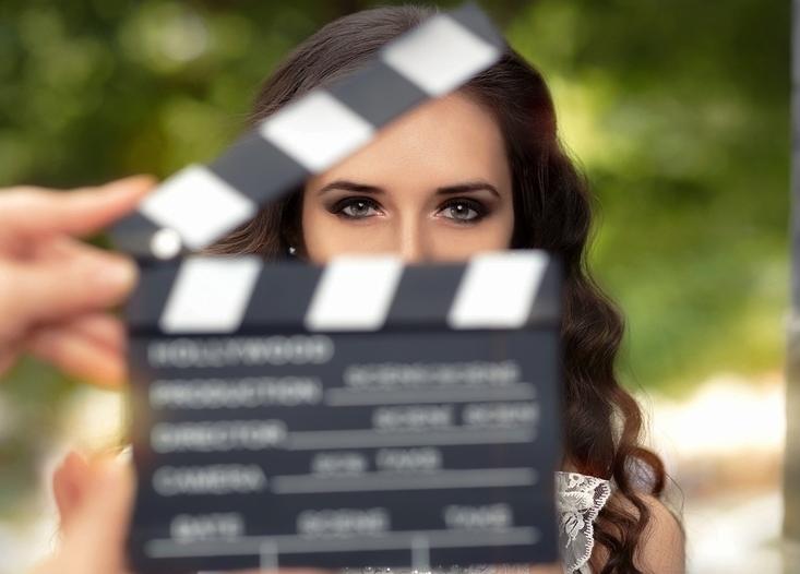 claqueta de cine cubre el rostro de una actriz mientras esta mira a la cámara intensamente.