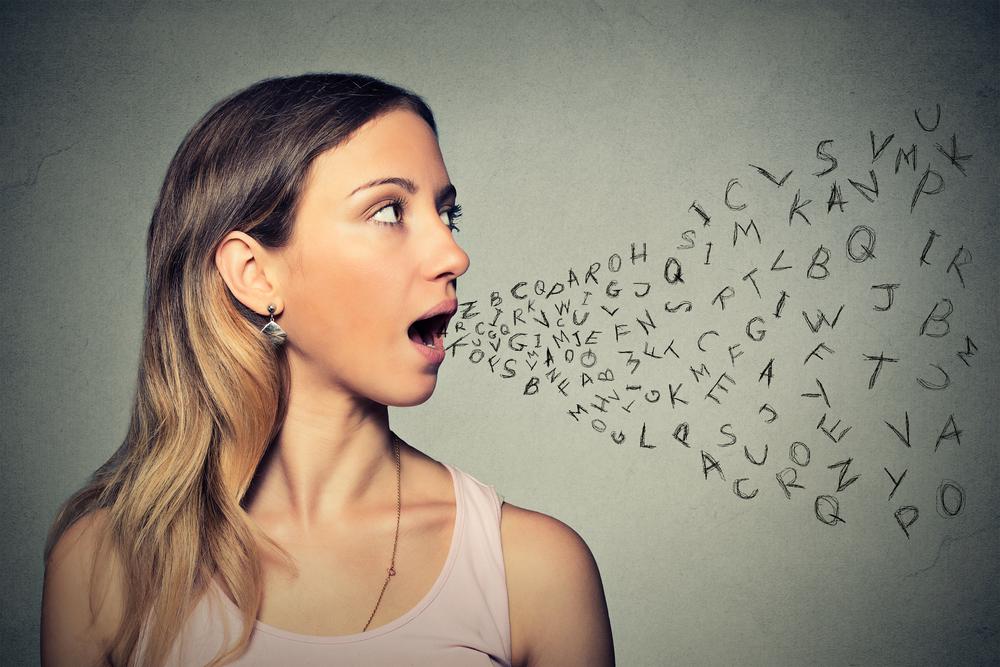 una mujer abre su boca y muchas letras dibujadas y en desordensalen de ella