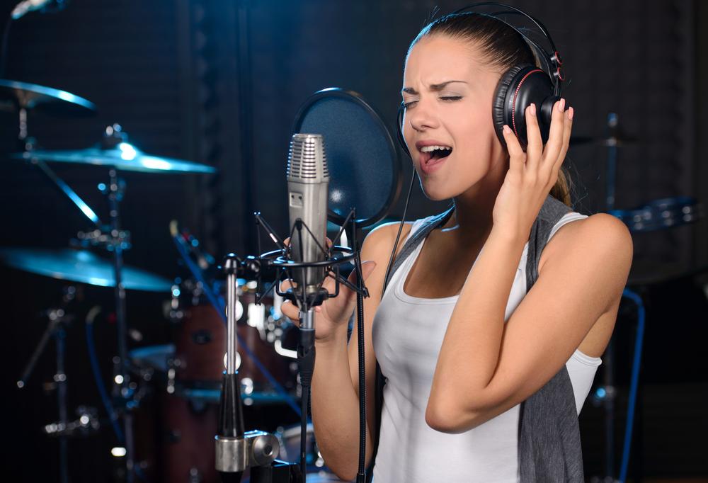 muchacha joven canta intensamente en un estudio de grabacion frente a un microfono mientras usa auriculares profesionales