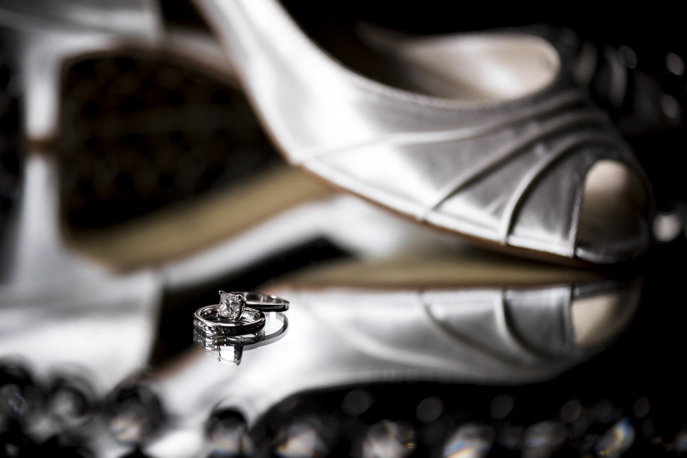 A wedding band and engagement ring in front of a pair of bride's wedding shoes