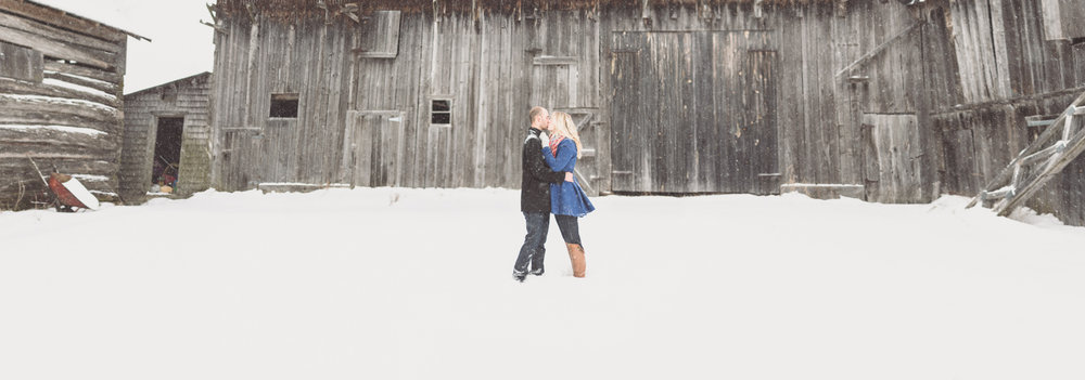 A winter engagement photo of a couple in front of a barn