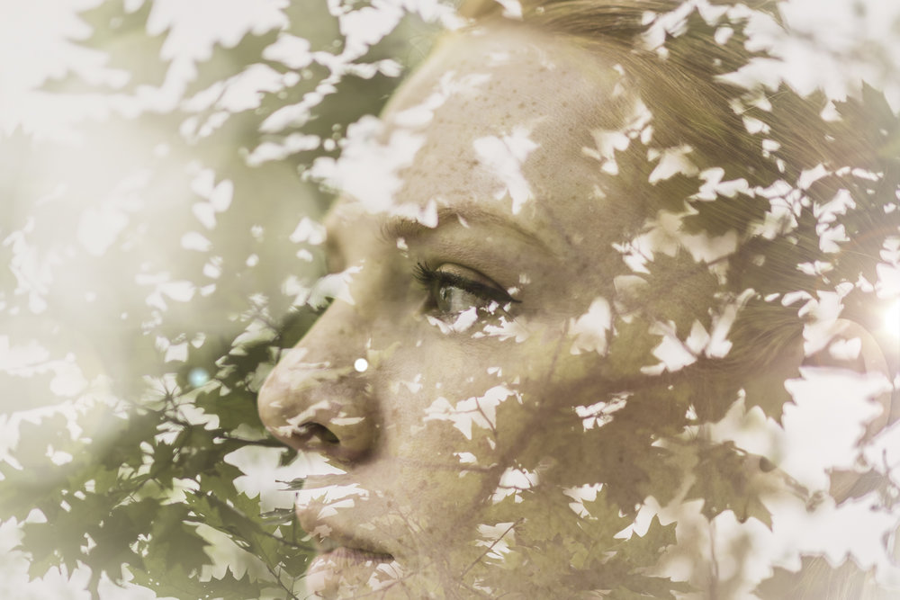 A double exposure of a woman and some leaves