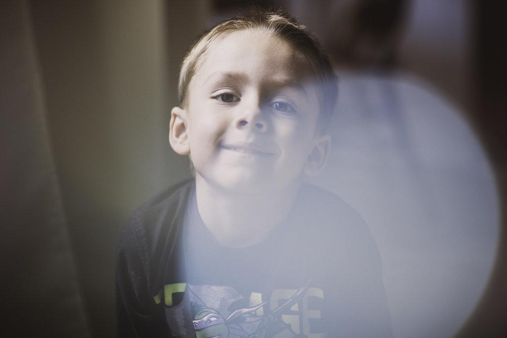 A boy near a curtain smiling