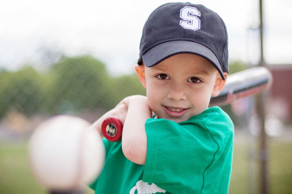 A little boy playing t-ball