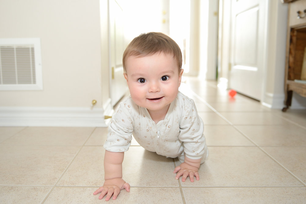 A little boy crawling on the floor towards the camera while smiling.
