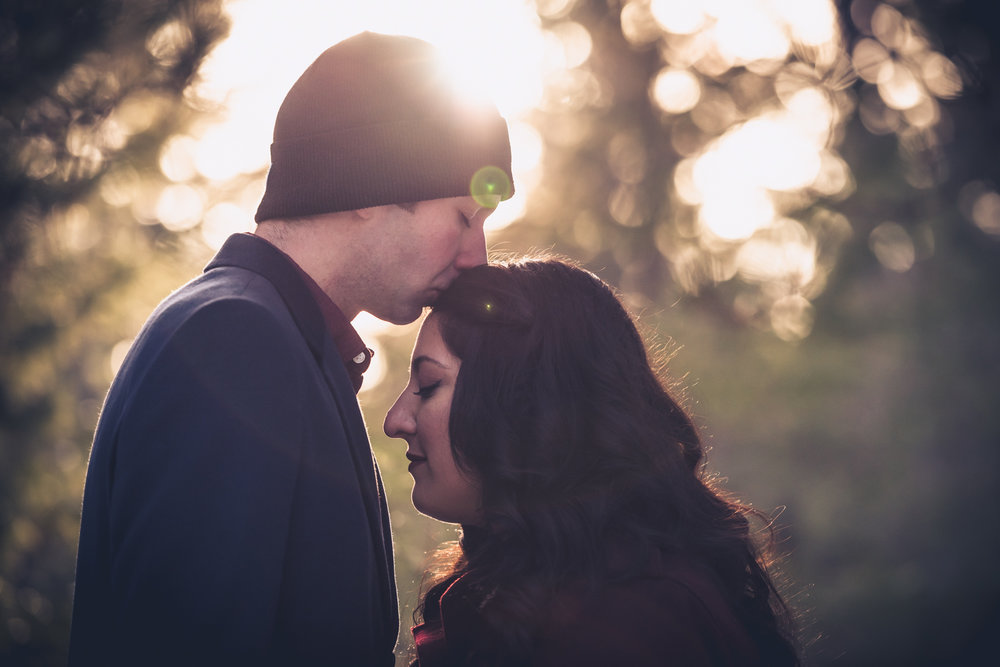 The couple kissing during a winter engagement photo shoot