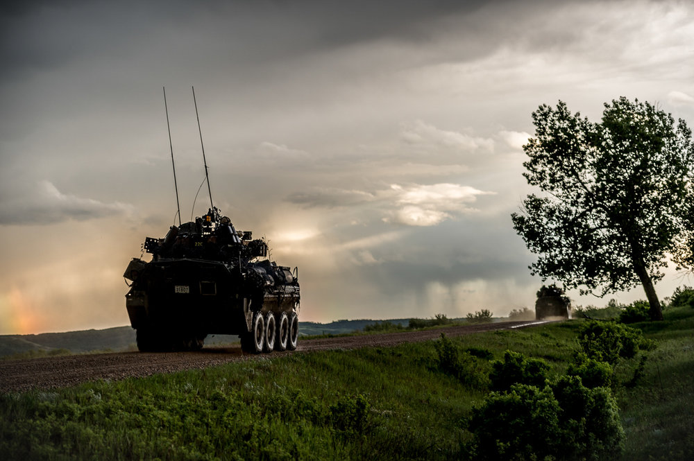 A Canadian Forces LAV rolling down a dirt road en route to secure a landing zone for parachute insertion.