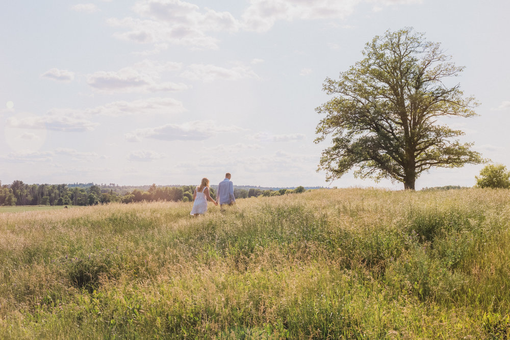 Jessalyn and Adam walking through a field.