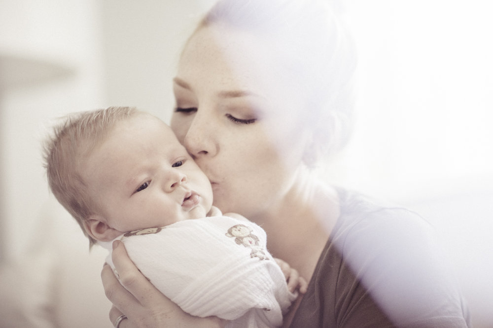 Whitney kissing baby John on the cheek.