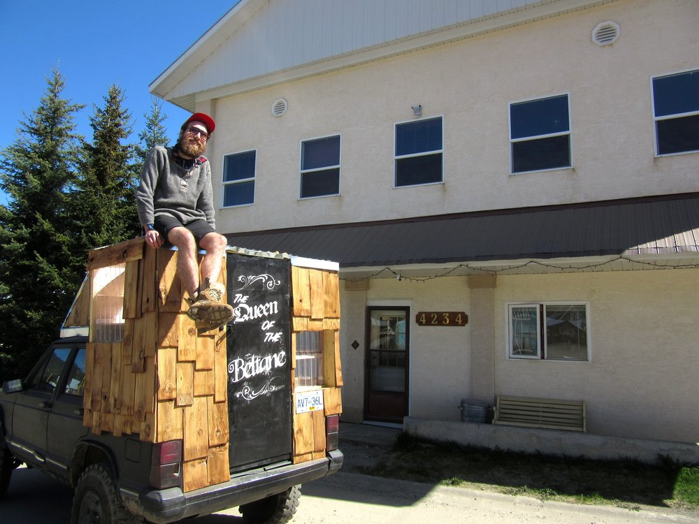 Aubrey Burke in front of Residence building and on top his homemade truck-camper. Photo by Ksenya Dorwart.