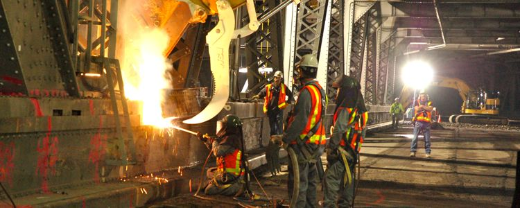THe first cut - Rushing oxygen super heats and blasts through the the first girders as workers prepare to remove the first section of bridge.