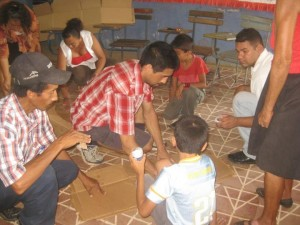The first workshop in Tipitapa: Andrew shows parents and children how to use cardboard as a means of physical therapy