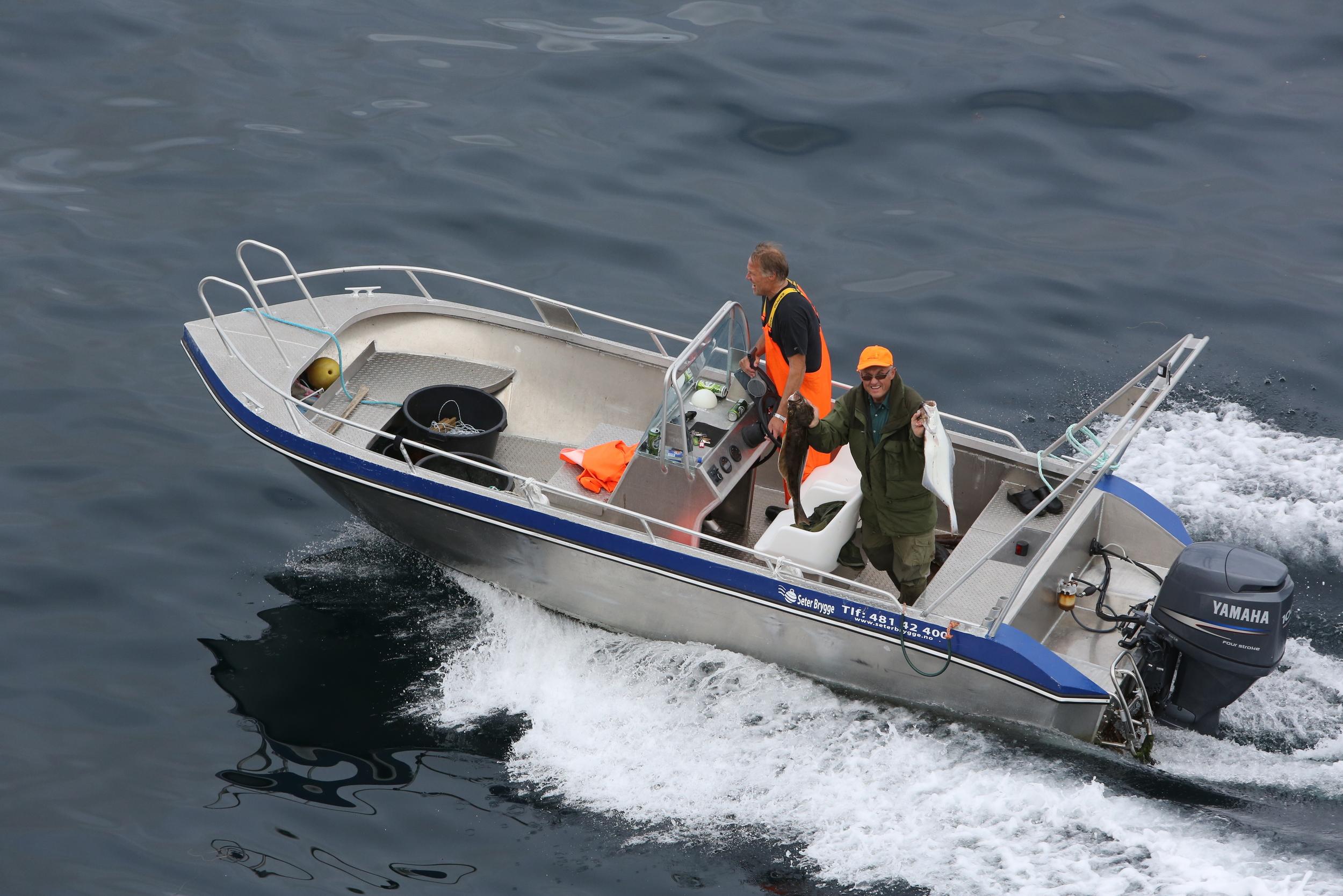 Glade turister viser frem fangsten