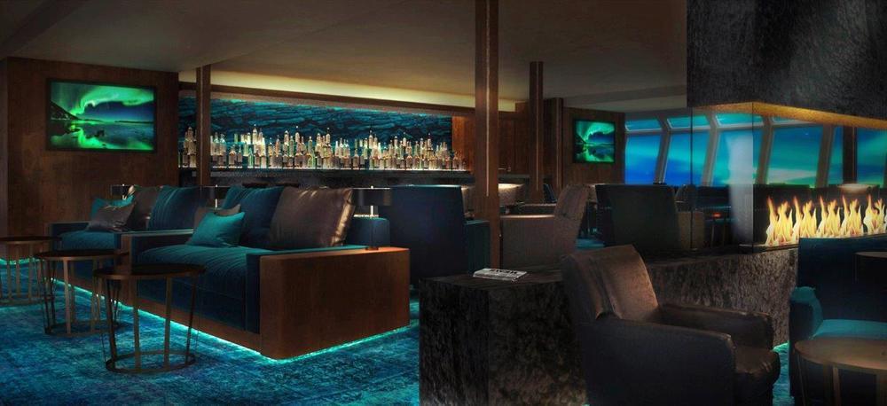 Norsk Offerdal-skifer rammer i illustrasjonen inn baren og peisen, og speiler landskapet utenfor. Komfortable møbler gjør at dette er et område hvor du ønsker å tilbringe tiden når man ikke er på utflukt, i havn eller på dekk.