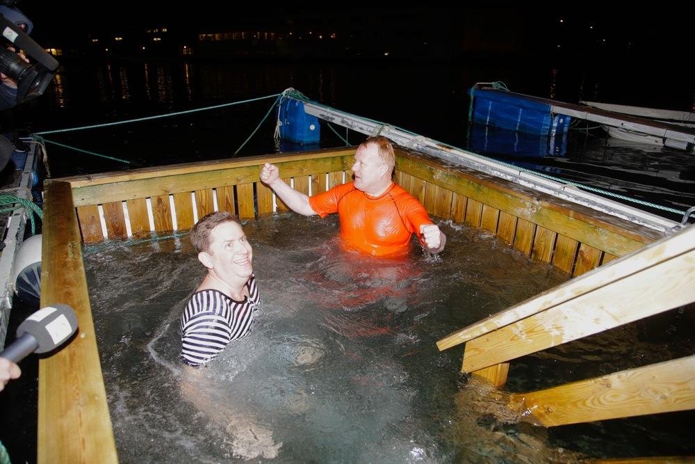 Hurtigrutens konserndirektør Daniel Skjeldam (tv) i retro-badetøy i havnebassenget i Vadsø. Temperatur i vannet: 2 grader.
