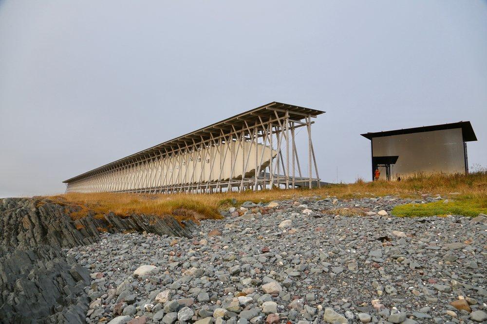 Minnehallen består av et langt furustillas. Mellom stokkene henger en kokong av tre som huser en svart, 125 meter lang gang, opplyst av 91 små glugger, ett for hvert offer.  Foto: Odd Roar Lange